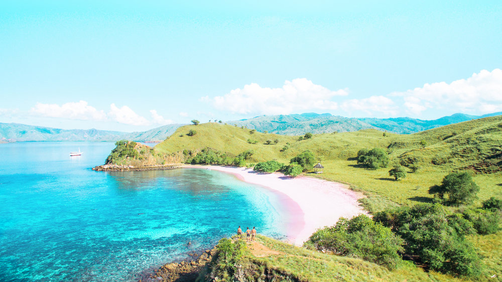 The pink beach looks wonderful surrounded by green hills