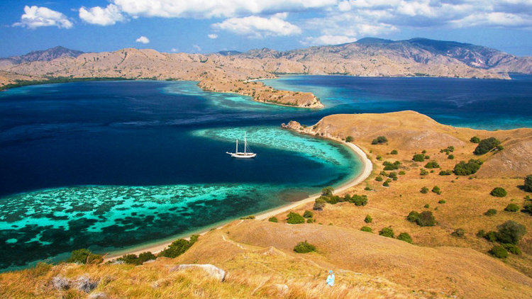 A boat is sailing near the shore of Gili Lawa Darat | Hello flores