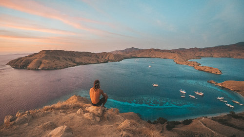 A man sitting on the hills of Gili Lawa Darat | Hello flores