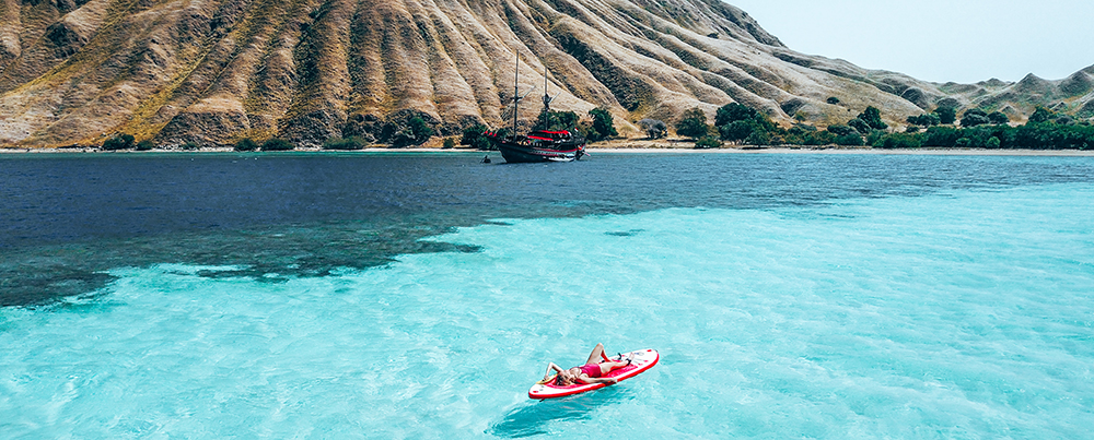 A woman is lying on a kayak on the Komodo sea