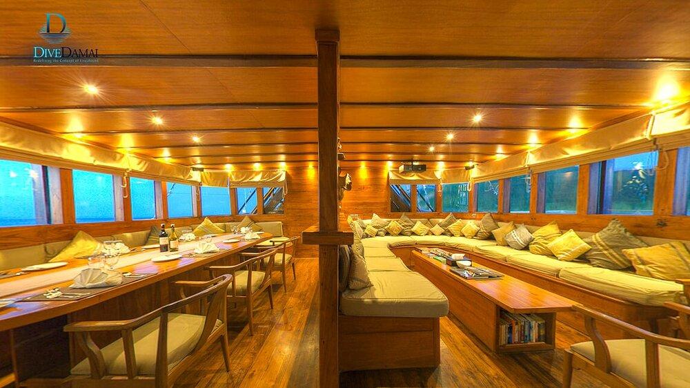 A giant lounge and dining area inside Damai II liveaboard | Hello Flores