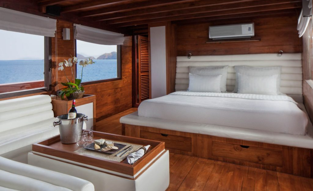 A nice bed and couch on the main bedroom of Samata liveaboard | Hello Flores