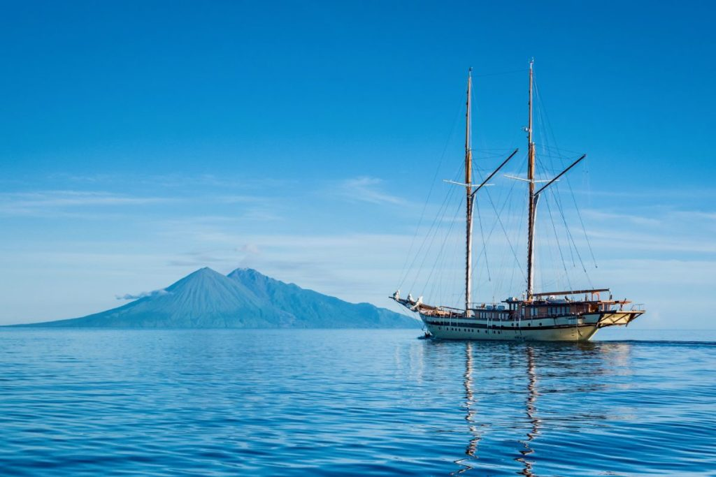 A modern Phinisi liveaboard with the sails down